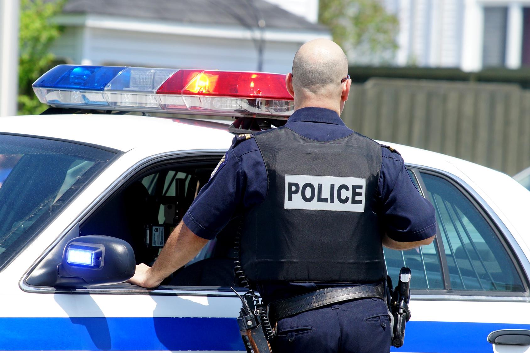 Policier devant voiture.